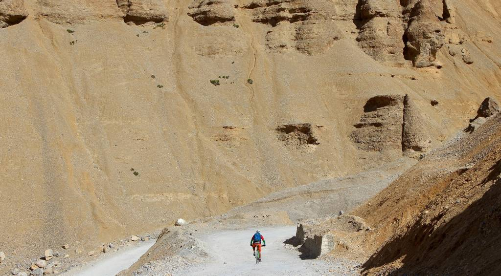 Mani Leh large cliffs and a lone cyclist in the distance